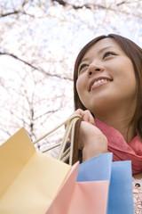 桜の下でショッピングバッグを持った女性