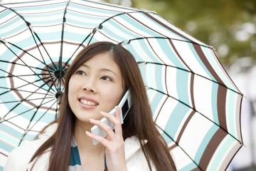 傘を差して携帯電話で通話する女性