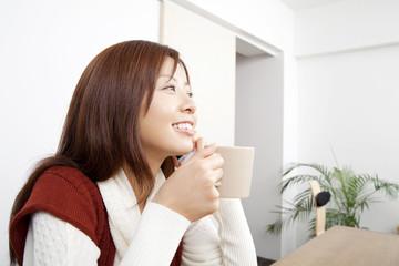 コーヒーを飲みながら携帯電話で通話する女性