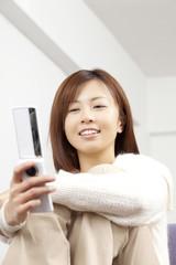 携帯電話でメールを確認する女性
