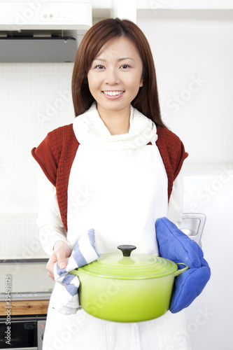 鍋を持って微笑む女性