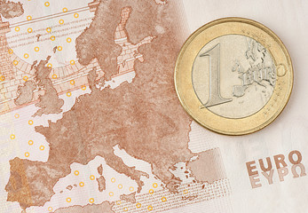 One Euro Coin on Euro Banknote showing Map of Europe