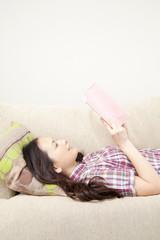 ソファに寝転んで本を読む女性