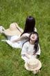 草原に背中合わせで座る女の子と若い女性