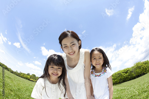草原で微笑む女の子2人と若い女性