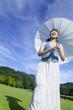 日傘をさして公園を歩く女性