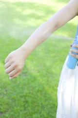 虫除けスプレーを腕にかける女性の手元