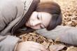 落ち葉の上で寝転がる女性