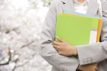 桜の下でファイルを持つ女性の手元