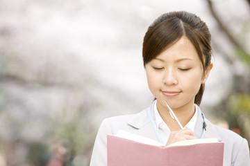 桜の下で考え事をする女性