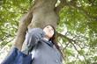 木に寄りかかる女子高生