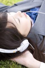 音楽を聴きながら寝そべる女子高生