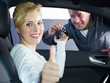Woman in car shows thumb up, motor mechanic hands her key