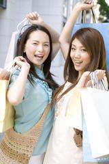 街中で買物袋を両手に持つ笑顔の女性2人
