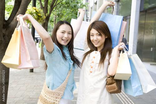 街中で買物袋を両手に持ってハシャグ2人の女性