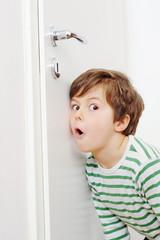 Junge lauscht an der Tür
