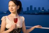 テラスでロゼワインを飲む女性