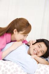 バスローブを着てベッドに横になる男女