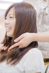 ヘアサロンで美容師に髪を梳かしてもらう女性