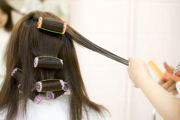 美容師にパーマをかけてもらう女性の後ろ姿