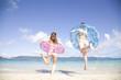 浮輪を持って海に入る女性2人の後ろ姿