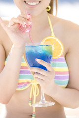 浜辺でデッキチェアに座りトロピカルジュースを飲んでいる女性