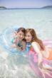 海で浮き輪に乗り手を伸ばす水着女性2人