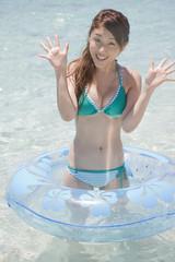 海に浮かべた浮き輪の中で立つ水着女性