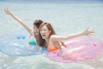 海で浮き輪に乗る水着女性2人
