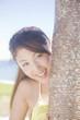 椰子の木から顔を覗かせる水着女性