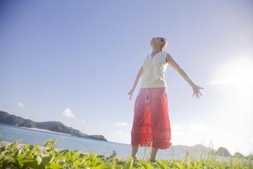 海辺で両手を広げ太陽の光を浴びる女性