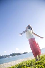海辺で両手を広げ太陽の光を浴びる女性の後姿
