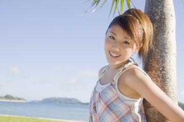 晴天の中椰子の木に寄りかかり微笑む女性