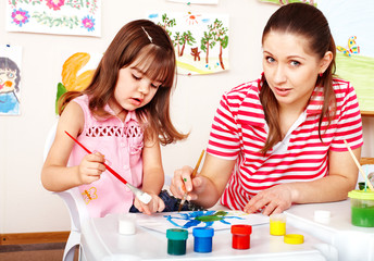 Child painting with mother  in preschooler.