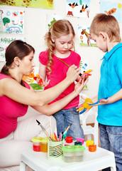 Children painting with teacher .