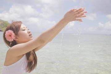 海水を手ですくう女性