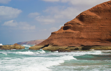 huge red cliffs with arches on the beach Legzira. Morocco