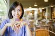 カフェで携帯電話を持って微笑む女性