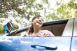 車の窓から体を乗り出す女性