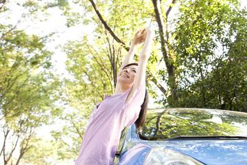 車に寄りかかってのびをする女性
