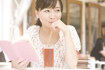 オープンカフェで読書しながら外を眺める女性