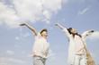 空に向かって両手を広げる女性2人