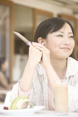 オープンカフェで外を眺める女性