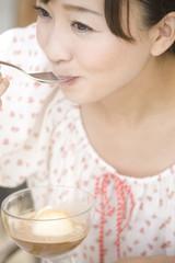 オープンカフェでデザートを食べる女性