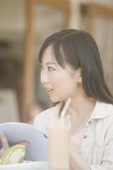 オープンカフェで友人と会話する女性