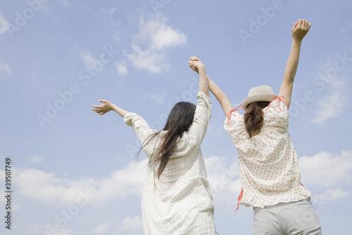 空に向かって両手を広げる女性2人の後ろ姿