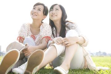 芝生の上に座って上を見あげる女性2人