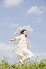 日傘を差してスキップする女性
