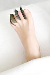 ホットストーンを足の指に挟んだ女性の足元