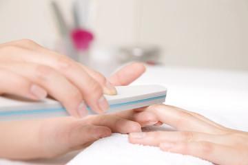 ネイルファイルで爪をこする女性の手元